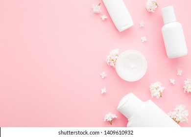 Different white toiletries and lilac branches with petals on light pink table. Care about face, hands, legs and body skin. Women beauty products. Empty place for text or logo. Flat lay.