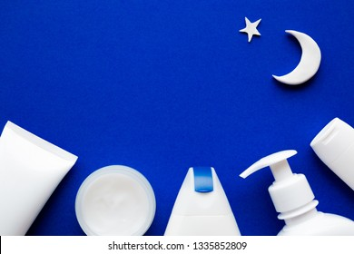 Different white toiletries, moon and star on dark blue background. Care about soft face, hands, legs and body skin in night time. Man's and woman's beauty products. Empty place for text or logo.