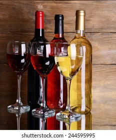 Different wine on table on wooden background