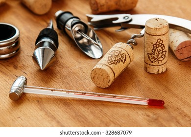 Different wine tools and corks on wooden surface