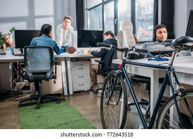 Differente people working at modern office with bicycle