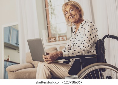Differently abled. Pretty blonde female sitting on wheelchair and looking straight at camera
