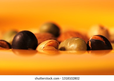 Differently colored dry soybeans on a blurred yellow plate
