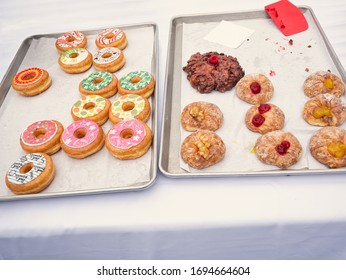 Differently decorated donuts distributed on a baking tray
