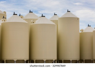 different-size beige grain bins stand vertically in a group