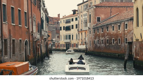 Differrent boats are moving along one of the water canals in Venice, Italy.