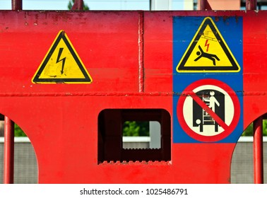 diffferent warning signs at a red painted train waggon