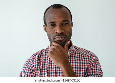 Difficult decision. Portrait of a thoughtful afro american man standing against white background while making a choice