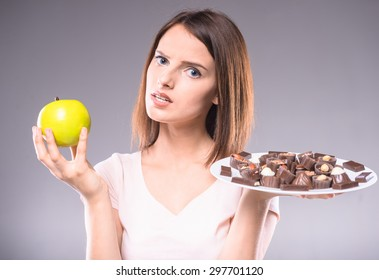 Difficult decision. Worried woman choosing between chocolates and  apple. Healthy lifestyle concept.