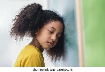 Difficult learning. Lazy student african girl bending her head on blackboard while the teacher is beginning to teach in classroom. School children education habit concept.