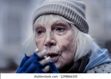 Difficult life. Portrait of a gloomy poor elderly woman breaking at her hands while trying to make herself warm