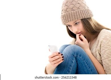 Difficult life situation, relationship problems. Sad teenage girl curled-up, looking at her smartphone, reading message, waiting for call, copy space