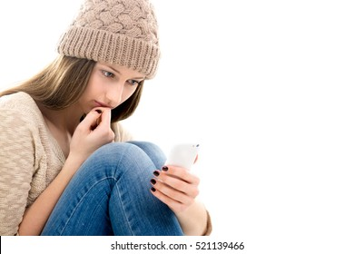 Difficult life situation, relationship problems. Sad teenage girl curled-up, hugging legs, feeling lonely, looking at smartphone, reading message, waiting for call, being bullied on-line. Copy space