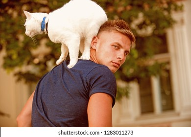 It is difficult to obtain the friendship of a cat. Happy cat owner with muscular look. Muscular man hold cute pedigree cat. Cat stands on back of his owner.