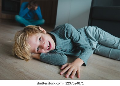 difficult parenting- father is tired while son smiles, makes mischief