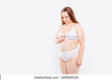 It's difficult to pick up bra. Concentrated confident chubby fatty with excess weight with sagged skin red-haired woman using a tape line to check the size of her breast, isolated on white background