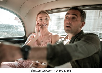 Difficult way. Worried man sitting at the backseat of the car with his wife and explaining the driver where to go pointing on the road.