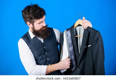 Difficulty choosing necktie. Shop assistant or personal stylist service. Matching necktie outfit. Man bearded hipster hold neckties and formal suit. Perfect necktie. Shopping concept. Stylist advice.