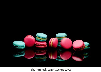 diffrent colorfull macarons on black background .pink color and ment color macaroons