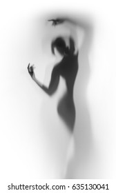 Diffuse silhouette of a beautiful dancer woman behind a curtain