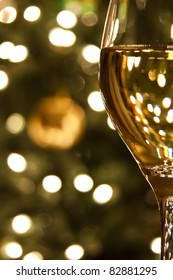Diffused lights and ornaments from a Christmas tree form the background for a close-up of a glass of white wine.