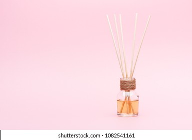 Diffuser Aromatic oil with Reed Sticks on a pink background
