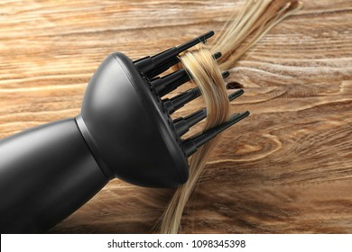 Diffuser hair dryer with strand of blonde hair on wooden background