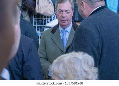 Digbeth, Birmingham / UK - April 13 2019: Head and shoulders of Nigel Farage flanked by members of his team and surrounded by members of the public at Indoor Market Birmingham.