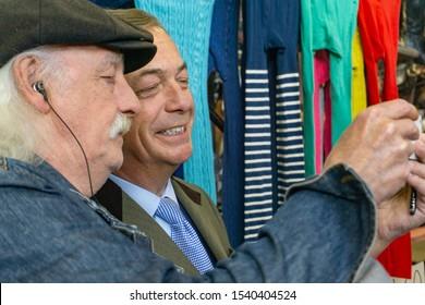 Digbeth, Birmingham / UK - April 13 2019: Head and shoulders, Nigel Farage poses for a selfie with a man at Indoor Market Birmingham