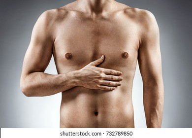 Digestion issue. Man holding his hand in area stomach. Medical concept.