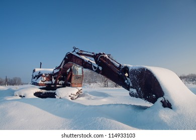 Digger bucket is left to the extended winter in field