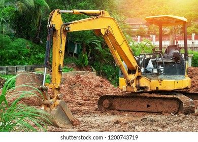 Digger machine  digging and removing earth adjusting ground level in construction site.Excavator in sunlight.