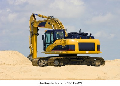 A Digger on top of a heap of sand