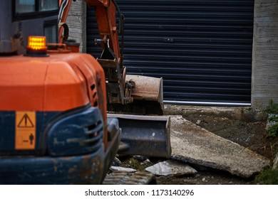 Digger ( partly out of focus ) in front of black dirty garage at concrete yard construction.