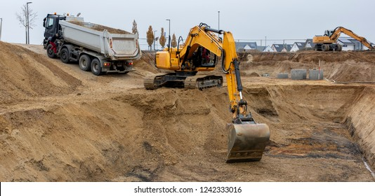 digger and truck working in excavation pit