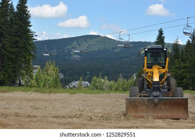 Digger vehicle in mountain with hills behind it