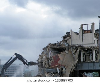 A digger working on a demolition site destroying a section of wall creating dust and rubble