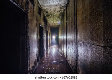 Diggers in flooded abandoned Soviet bunker tunnel with metal walls