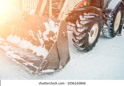digging the earth in winter. Tractor works on the construction site in the cold winter Construction and snow removal equipment at the plant - loader with snow unloading during roadworks