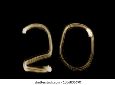Digit 20 twenty. Two and Zero, Null. Glowing numbers on dark background. Abstract night light painting. Creative artistic golden bokeh.