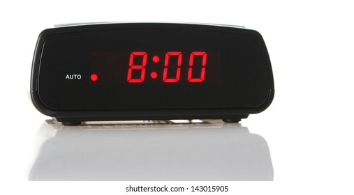 A digital alarm clock showing 8:00am over white background with a natural reflection under it.