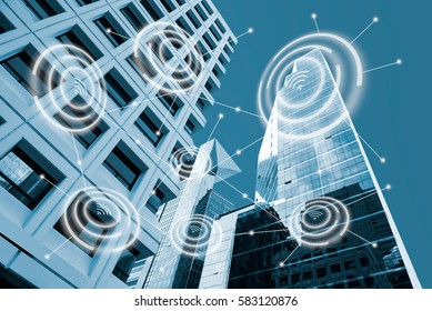 Digital alarm icon and low angle view modern office buildings in blue tone  with network connection concept,  smart city and wireless communication network, IOT internet of things conceptual image