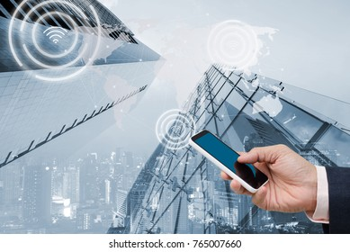 Digital alarm icon on city background, mobile smart phone computer device with network connection, smart city and wireless network communication, IOT internet of things conceptual image