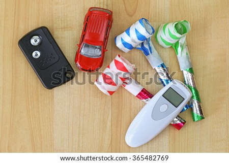 Digital Alcohol Breath Tester Device In White Next To A Car Remote Key And Colorful Party