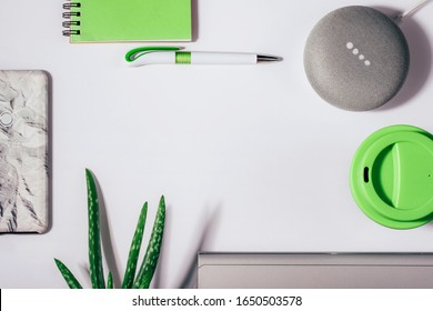 Digital Assistant concept. Flat lay of smart speaker with LED lights activated with cropped smartphone, green notepad, pen, aloe vera plant and reusable coffee cup.