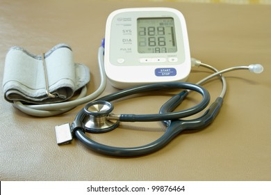 Digital blood pressure meter and stethoscope rest on the bed