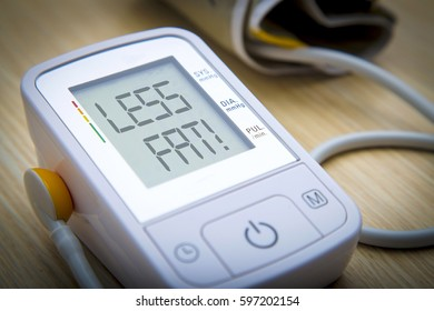 Digital blood pressure meter with warning message LESS FAT on the monitor. Health hazard concept