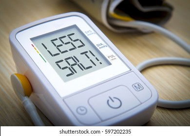 Digital blood pressure meter with warning message LESS SALT on the monitor. Health hazard concept
