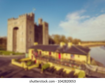 Digital blurred defocused background Aerial view of Ireland's most famous Castle and Irish Pub in County Clare. Famous world tourist attraction. Bunratty Castle and Durty Nelly's Pub.