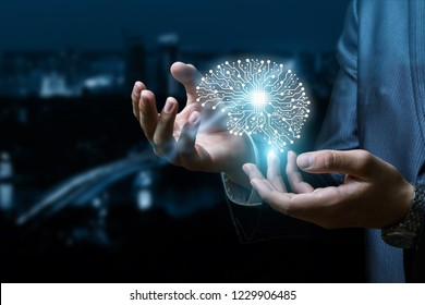 A digital brain model is going up from the businessman 's hands at the busy night city background. The concept is the extensive unconventional thinking.